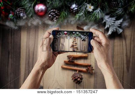Smartphone take shot Christmas fir tree made from spices cinnamon sticks anise star and Christmas decoration of fir tree and conifer cone on texture wood background.
