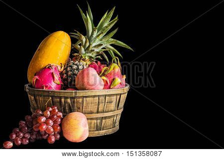 Many fruits in a basket on a black background.