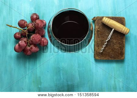 Vibrant photo of a glass of red wine with a bunch of grapes and a vintage corkscrew on an old notebook, shot from above on a turquoise blue wooden background texture, with copyspace