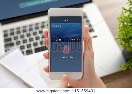 female hand holding white phone with touch and pay on screen near notebook