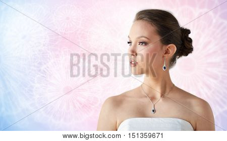 beauty, jewelry, wedding accessories, people and luxury concept - beautiful asian woman or bride with earring and pendant over rose quartz and serenity patterned background