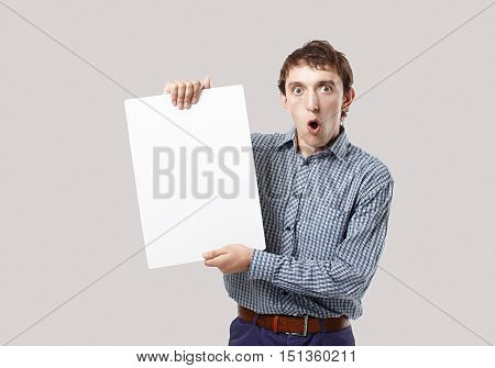 shocked man with a sheet of white paper in hands. guy opened his mouth in surprise. young man holding a blank sheet of white paper for your text. looking at camera. mockup. isolated on grey background