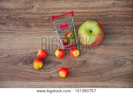 One big apple and several small laying on brown wooden table near small shopping cart with red strawberries in it