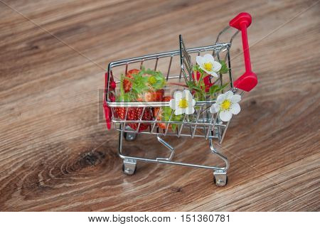 Small shopping cart with red strawberries and flowers inside on brown wooden background. Focus on flowers