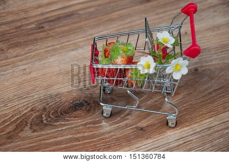 Small shopping cart with red strawberries and flowers inside on brown wooden background. Focus on berries