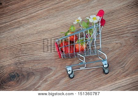 Shopping cart with strawberries inside laying on wooden background. Top view
