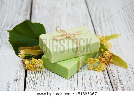 Handmade linden Soap with linden flowers on a old wooden table