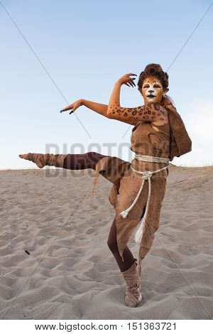 Human cheetah woman dances in desert sand