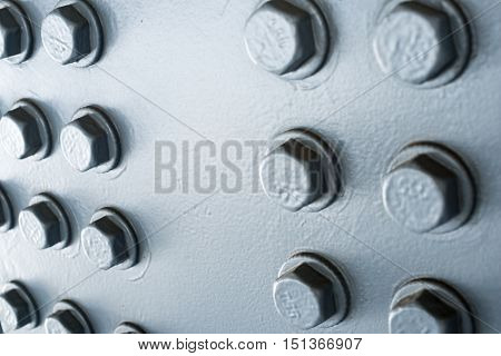 Gray painted metal surface with hexagonal bolt heads.
