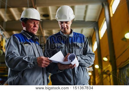 Two workers in overalls holding documents and looking at them in the premises of the factory