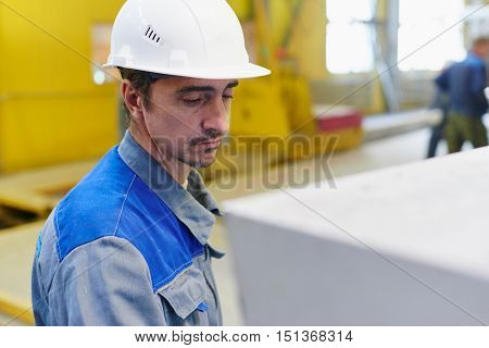 Worker in overalls and helmet in the premises of the plant