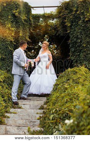 Newlyweds on a walk in the summer day wedding