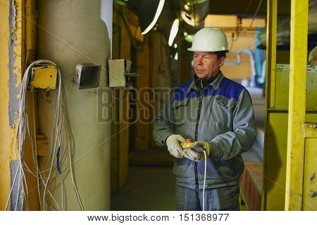 A man in overalls and a helmet holding a remote control in the workplace