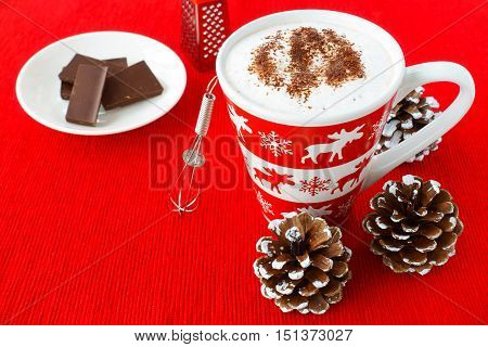 Hot Chocolate with foamed milk sprinkled with grated chocolate in a festive mug with winter motives and a small whisk chocolate and chocolate grater on red place mat surrounded by snowy pine cones.