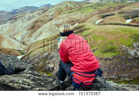 woman hiker photographer taking picture on the mountains background in Iceland