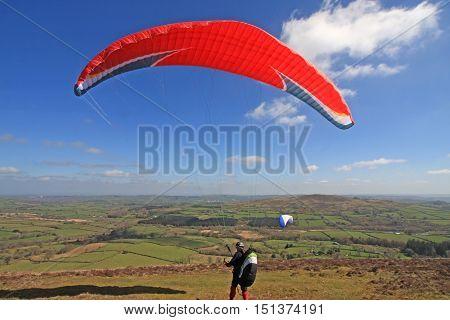 Paraglider launching his wing on Dartmoor, Devon