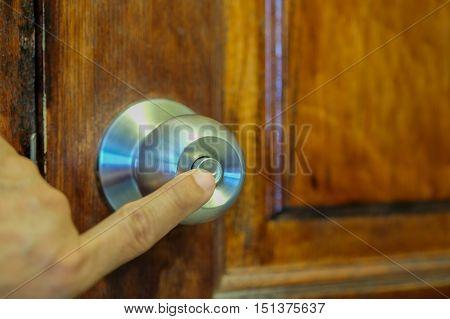 Hands are locked door knob for security.