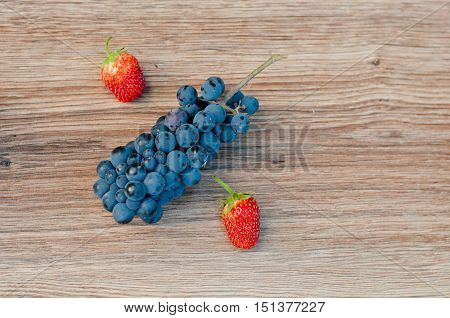 Symbol percent made of blue grapes and red strawberries on brown wooden background. Top view. Space for text