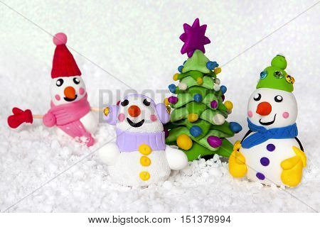 New Year tree and cheerful snowmen from plasticine on a snow white background.