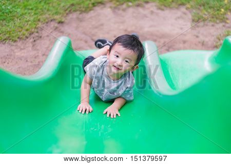 Little Asian Kid Climbing Up The Slide At The Playground In Summer, Shallow Dof