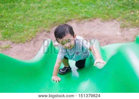 Little Asian kid climbing up the slide at the playground under the sunlight in summer, Kids play on school yard. Happy kid in kindergarten or preschool. shallow DOF