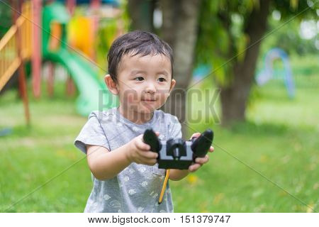 Little Asian Kid Holding A Radio Remote Control (controlling Handset) For Helicopter , Drone Or Plan
