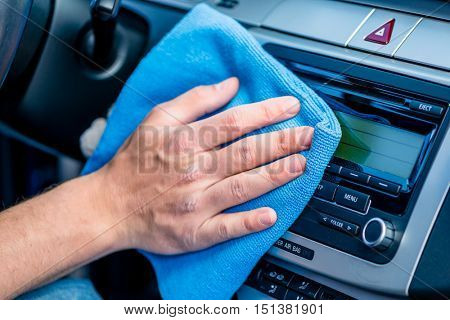 Man wiping the display glass on the dashboard in his car with a blue anti-static cloth as he cleans the vehicle, close up on his hand