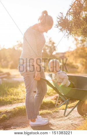 Adorable toddler boy and his mother walking along country road. Child sitting in a wheelbarrow. Summer works in the garden. Happy family on the sunset.