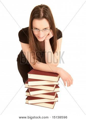Young Student With Glasses And A Pile Of Books