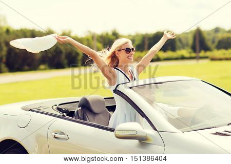 transport, leisure, road trip and people concept - happy man and woman driving in cabriolet car outdoors