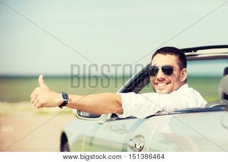 auto business, transport, leisure and people concept - happy man driving cabriolet car and showing thumbs up