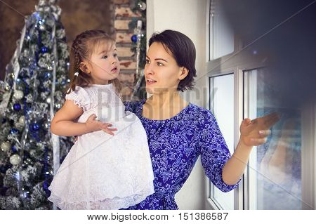 Happy mother and her little daughter by the Christmas tree looking at the window