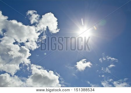 Blue sky and bright summer sunshine with white soft focus clouds