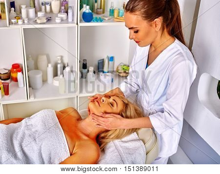 Woman middle-aged take face and neck massage in spa salon. Interior with lot of cosmetic bottles.