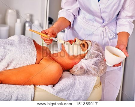 Woman middle-aged take facial and neck clay mask in spa salon. Interior with lot of cosmetic bottles.