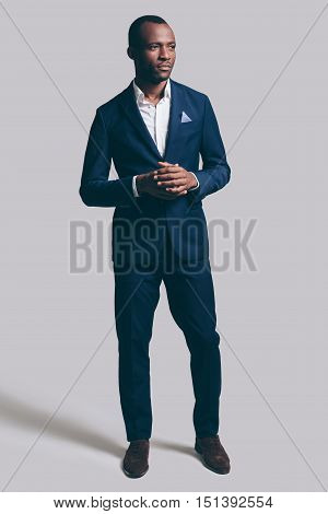 Confidence and charisma. Full length of handsome young African man in full suit holding hands clasped and looking away while standing against grey background