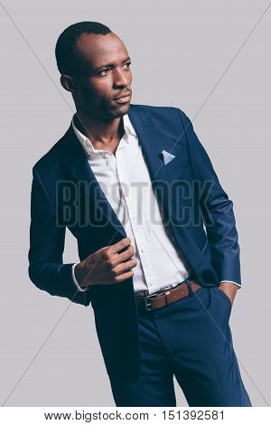 Used to look perfect. Handsome young African man in full suit adjsuting his jacket and holding one hand in pocket while standing against grey background