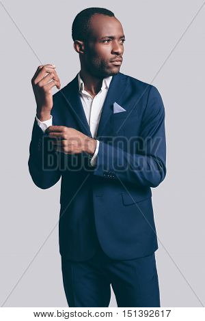 Perfect style. Handsome young African man in full suit adjusting his sleeve and looking away while standing against grey background