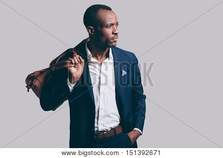 Confident in his perfect style. Handsome young African man in full suit carrying brown leather bag on shoulder and looking away while standing against grey background