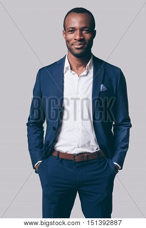 Handsome man. Handsome young African man in smart casual jacket holding hands in pockets and smiling while standing against grey background