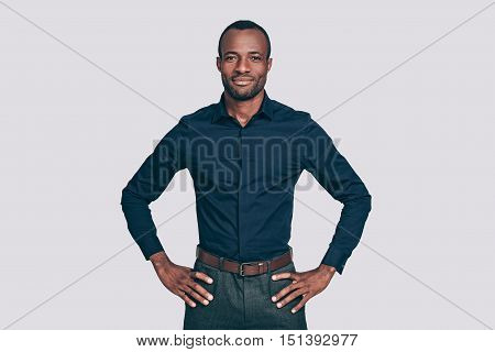 Confident young man. Handsome young African man keeping arms crossed and looking at camera while standing against grey background