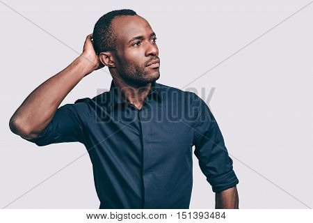 Thinking about business. Thoughtful young African man holding hand on head and looking away while standing against grey background