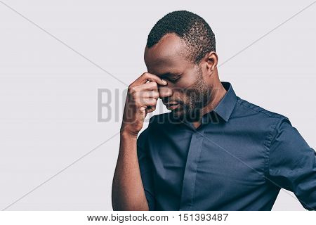 Stressed and tired. Frustrated young African man massaging nose and keeping eyes closed while standing against grey background