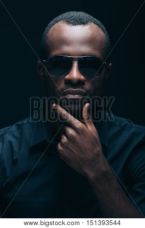 Trendy look. Portrait of handsome young African man holding hand on chin and looking at camera while being in front of black background