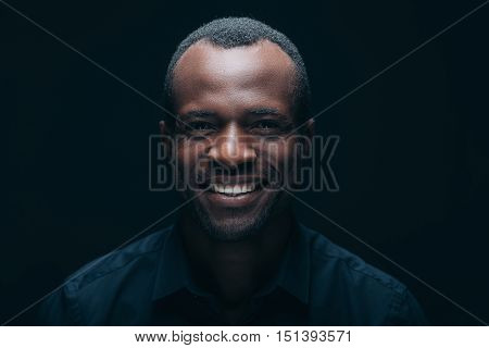 Cheerful young man. Portrait of handsome young African man looking at camera with smile while being in front of black background
