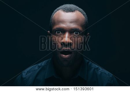 No way! Portrait of surprised young African man looking at camera and keeping mouth open while being in front of black background