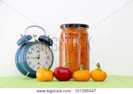 picture of a Traditional Macedonian food. Ajvar in jar alarm clock and chilli peppers on green . homemade product.food concept