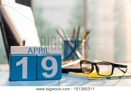 April 19th. Day 19 of month, calendar on business office background, workplace with laptop and glasses. Spring time, empty space for text.