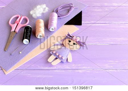 Set for kids activity and creativity. Felt doll, scissors, thread, needles, pins, pliers, suede cord, felt sheets on wooden background with empty space for text. Easy kids diy