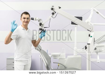 Happy dentist stands in the clinic on the background of the dental equipment. He shows OK symbol and looks into the camera with a smile. Man holds dental microscope with left hand. Horizontal.